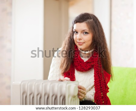 Long-haired woman near oil heater in home