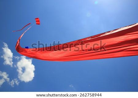 Long red kite against a vivid blue sky.