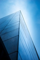 Looking up at the city's tall buildings from a low angle, the side of the building has a triangular pyramid