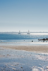 Lorient, Larmor Plage, beach, low tide with sailing boats in sunlight
