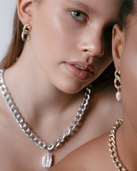 ?lose-up portrait of africans and europeans girls in jewelry on neck and fashionable make up. Two beautiful girls of different races dark skinned and white skinned with nutural make up