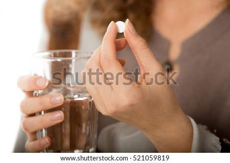 �¡lose-up view photo of female hands holding one white round pill and glass of water. Young woman taking medication, feeling ill. Healthcare concept