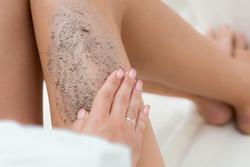 Сloseup woman legs with coffee massage scrub. Cosmetology, grooming, Spa cosmetic products, beauty and bikini concept.