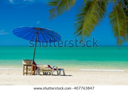 lounge chairs with sun umbrella on the tropical  beach #407763847