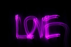 'Love' word written in pink light on black background. Long exposure  neon light photograph. February 14 Valentine's Day concept. Neon wallpaper.