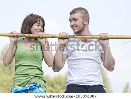 Loving couple hanging on the crossbar