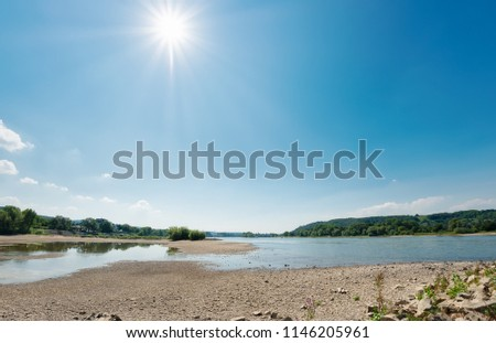 \nLow water level in the dried-out riverbed of the river Rhine between groins on a sunny day, caused by prolonged drought, North Rhine-Westphalia, Germany, Europe