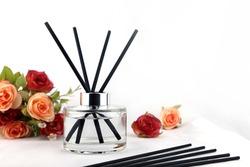 ชื่อผลงาน: luxury aroma scent reed diffuser glass bottle is on the white table with roses flowers to creat romantic and relax ambient in the bedroom with white cement wall background on the happy vale
