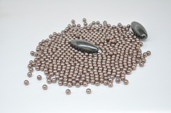 Magnet, two oval magnet with bijouteral balls beside on white background with selective focus