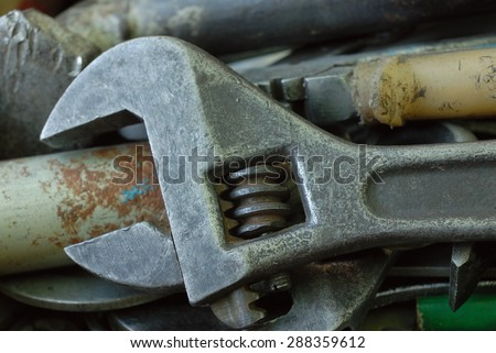 Main part of old adjustable wrench and another working tools as background.