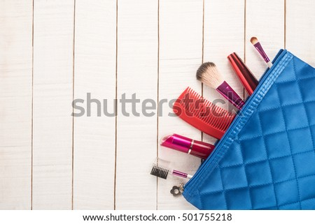 Make up bag with cosmetics on wooden background #501755218