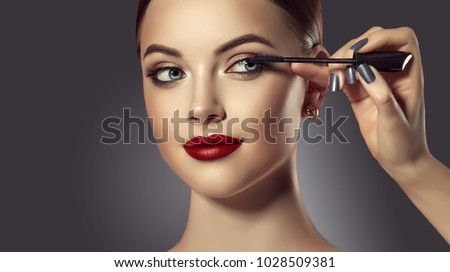 Makeup artist applies mascara to the eyelashes of the  model girl . Beautiful woman face. Hand of make-up master painting,  make up in process.  #1028509381