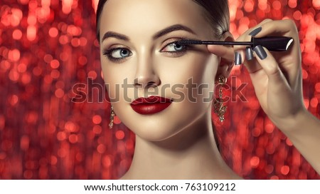 Makeup artist applies mascara to the eyelashes of the  model girl . Beautiful woman face. Hand of make-up master painting,  make up in progress .