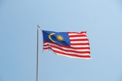 Malaysian flag waving in the wind with clear blue sky