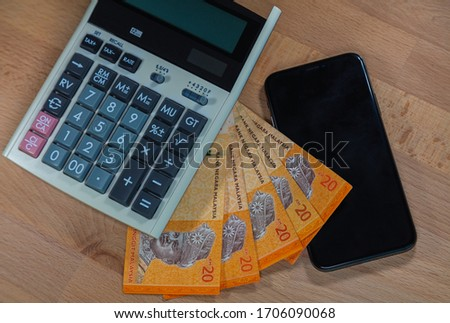 20 malaysian Ringgit on a wooden desk, surrounded of calculator and a mobile phone.  Close up macro photography of money and office Utils on a wood table. Ringgit Malaysia with calculator and phone.