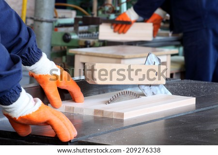 male carpenter using table saw for cutting wood 5