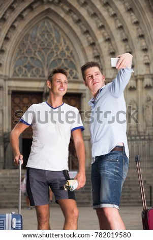 Male couple with luggage doing selfie picture at travel destination background  #782019580