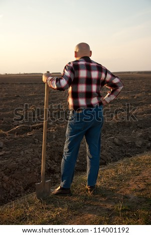 male farmer holding   shovel and looking at sky