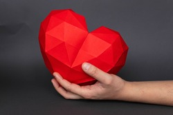 Male hand holds red heart shaped polygonal paper on gray background. Red polygonal paper heart for Valentine's Day or any other love invitations. Holiday and medicine concept.