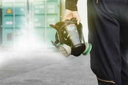 Male industrial technician who holds a respirator mask, an ammonia odor mask, NH3 to control and fix leaks inside the factory's container : Copy Space