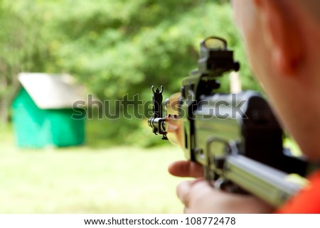 Man aiming at a target and shooting an automatic rifle for strikeball. Focus on the rifle sights.