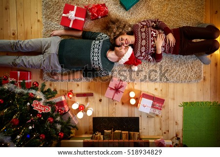 Man and woman lying on the floor in Christmas decorated home