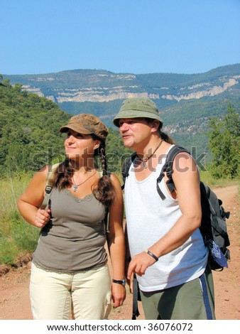 man and  woman tourists on walk in mountains Pyrenees