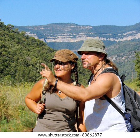 man and  woman tourists on walk in mountains Pyrenees, Spain - stock photo