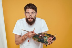 man artist with an easel on a yellow background