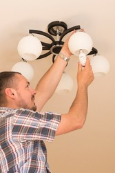 Man changes an electric light bulb, energy efficiency. Closeup of man's hand adjusting electric bulb by pendant lights at home. Electrician