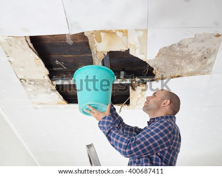 Man Collecting Water In Bucket From Ceiling. Ceiling panels damaged  huge hole in roof from rainwater leakage.Water damaged ceiling .