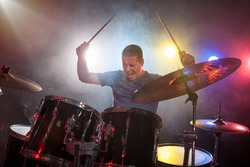 man drummer playing drums with passion over dark background