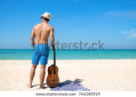 man enjoy with the nature at the sea beach with guitar in hand, daylight sunny enjoyment #766280929