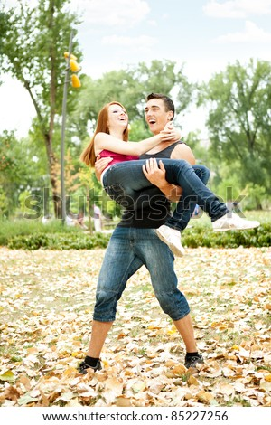 man holding girlfriend in his arms, both laughing