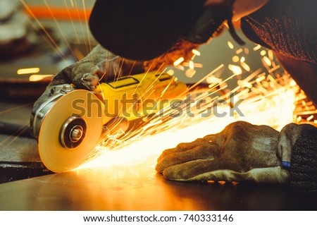 man in ordinary clothes and protective glasses with angle grinders while working in the workshop cutting metal