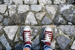 man legs in sneakers standing on stone stairs