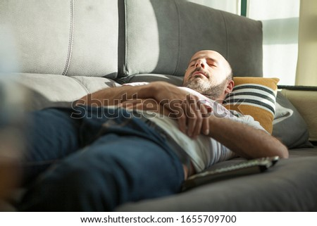 Man napping on the sofa at home