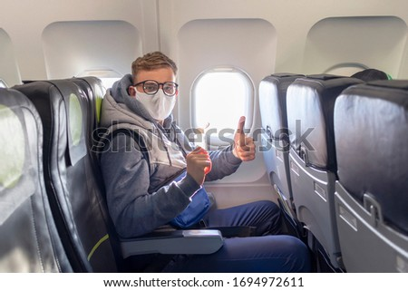 man on airplane show thumb up in glasses, medical protective sterile mask on his face sitting on plane using, apply anitizer for disinfect hands against coronavirus, virus bacteria. Pandemic covid-19 Foto stock ©