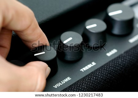 man's hand is adjusting the music volume from the amplifier. #1230217483
