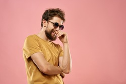 man shaggy with glasses laughing on a pink background