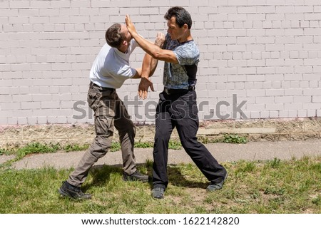 Man strikes back to aggressor with palm in forehead and nose. Martial arts instructors demonstrate self-defense techniques of Krav Maga