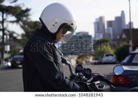 Man tries to put in his helmet while standing beside motorcycle