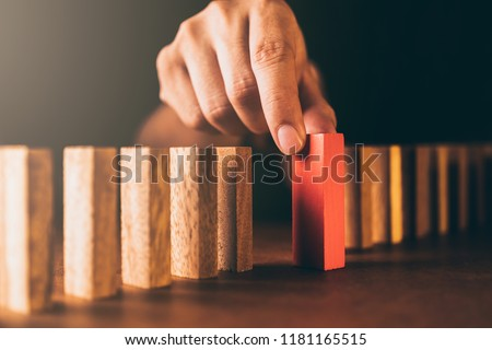 man try to build block on wooden table and black business man try to choose red color wood block from others on wooden table and black background business organization startup concept