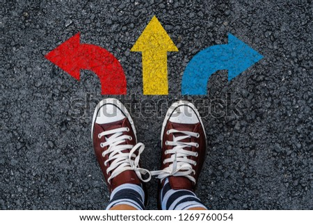 man with a shoes  are standing next to three direction colorful arrow choices, left, right or move forward