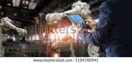 Manager engineer check and control automation robot arms machine in intelligent factory industrial on real time monitoring system software. Welding robotics and digital manufacturing operation.  Stockfoto ©