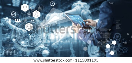 Manager Technical Industrial Engineer working and control robotics with monitoring system software and icon industry network connection on tablet. AI, Artificial Intelligence, Automation robot arm.  #1115081195
