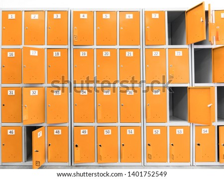 many orange cabinets, safe deposit boxes with keys for storing things in the supermarket and store. Safes for buyers