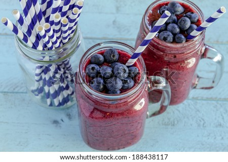 2 Mason jars filled with blueberry and blackberry fresh fruit smoothie sitting on blue wood background with straws