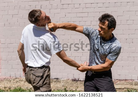 mature man attacks a young man, strikes, fixing the opponent's hand. Martial arts instructors demonstrate self-defense techniques of Krav Maga