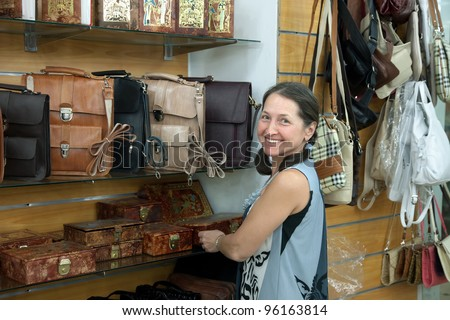 Mature woman chooses leather chest at  shop